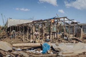 Nainen seisoo Idai-hirmumyrskyn tuhoaman talon edessä.