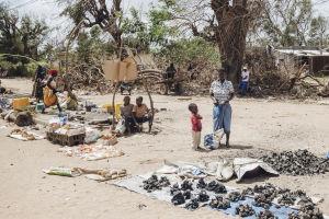 Ihmisiä kylänraitilla Mosambikissa. Kuvan keskiössä nainen ja poika sekä hiilikasoja.