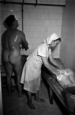 Elannon sauna. Helsinginkatu 2. Kylvettäjä pesee penkillä makaavaa miestä taustalla toinen mies suihkussa.