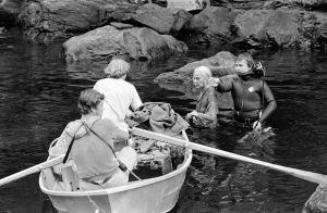 Rauta-aika tv-sarjan kuvaukset Imatrankoskessa. Näyttelijä Soli Labbart roolissaan Lemminkäisen äitinä seisoo vedessä, mies sukelluspuvussa opastaa. Vieressä soutuvene, jossa valaisija Kauko Myrskyranta ja pukusuunnittelija Riitta Riihonen.