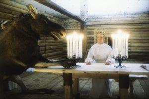 Näyttelijä Pirkko-Liisa Tikka morsiamen roolissa tv-sarjassa Rauta-aika. Hirvi ja morsian pöydän ääressä.