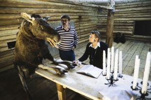 Hirvi, pääjärjestäjä Raimo Mikkola ja ohjaaja Kalle Holmberg työssä pöydän ääressä Rauta-aika tv-sarjan lavasteissa.