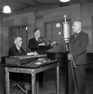 A. O. Väisänen radion studiossa mikrofonin ääressä. Vas.Matti Koskinen soittaa kanteletta ja Tapio Savioja viulua,