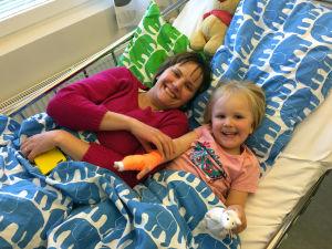 Mamma och hennes treåriga dotter ligger på en sjukhussäng, de ler mot kameran
