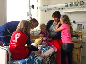 en treårig flicka på sjukhussängen tillsammans med sina syskon, mamma och läkare