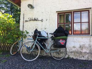 Pyörät nojaavat valkoiseen kiviseinään, jossa lukee sauna.