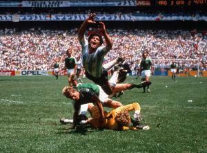 Jalkapalloilija Diego Maradona kaatuu saksalaisten pelaajien, Harald Schumacherin ja Karl-Heinz Försterin yli vuoden 1986 Meksikon maailman mestaruuskisoissa.