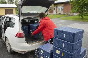 ruokapakkauksia lastataan autoon