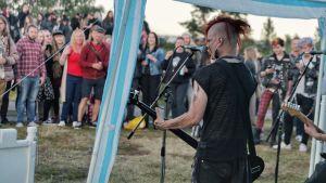 En bassist spelar framför en publik inne i ett tält