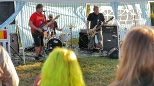 En publik står och tittar på ett band inne i ett tält