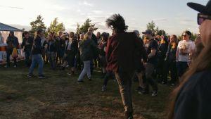 En grupp springer runt i cirkel framför ett band