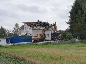 Grävmaskin framför det brandskadade huset.