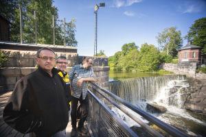 Kari Stenholm t.v., Markku Marttinen i mitten, Henrik Kettunen t.h. Tre män står vid en fors. Det är en solig dag. Männen ser allvarliga ut.
