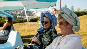 Kaksi naista istuu pyyhkeet päässä