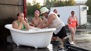 Äiti kylpee ja lapsi pumppaa suikusta vettä
