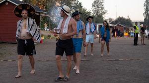 Miehiä kävelee hatut päässä