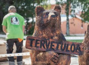 Puusta veistetty karhu jolla kyltti jossa teksti Tervetuloa, taustalla vihreään paitaan pukeutunut mies selin