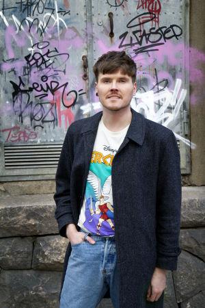 Eino Nurmisto seisoo graffitiseinän edustalla.