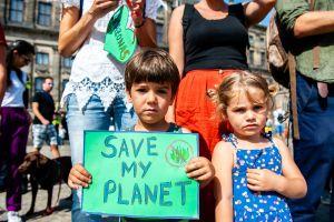 """Ett barn håller en skylt med texten: """"Rädda min planet"""" i Amsterdam."""