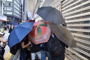 Ungdomar såg med sina paraplyer till att det var omöjligt att identifiera personen som målade graffiti på Bank of China.
