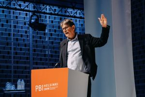 Man on stage, raising his left hand i a gesture behind the PBI podium on stage.