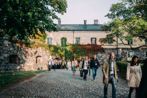 A group of people walking outside a court yard at Suomenlinna fortress.