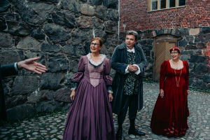 Three people in medieval dressed in a court yard in Suomenlinna.