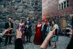 A group of people in medieval dresses in a courtyard. People with mobile cameras taking photos of them.