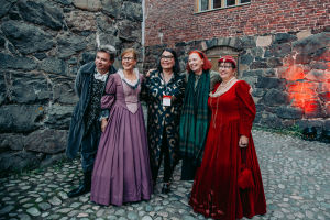 A group of people in medieval dresses in a courtyard.