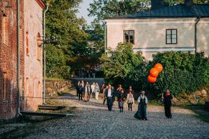 A person with three orange ballons leading a group of people in Suomenlinna.
