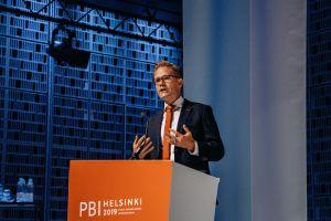 A man speaking with his hands raised behind an orange podium.