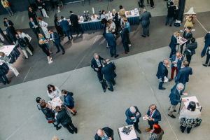 A birds eye view of people talking to each other on a grey concrete floor.