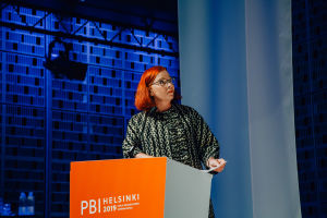 A woman behind an orange podium on stage, looking towards what seems to be a screen.