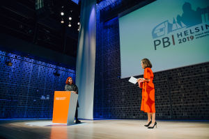 A woman in an orange dress talking to another woman behind an orange podium on stage.