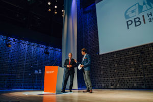 Two men talking to each other behind an orange podium on stage.