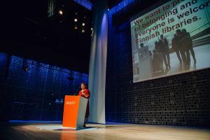 A woman speaking behind an orange PBI Helsinki 2019 podium.