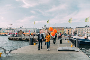 People walking on a dock. Three orange ballons in the foreground.