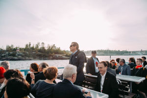 A man standing on an outside deck on a ferry. More people sitting down.