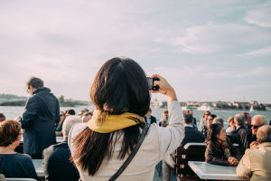 A woman taking a selfie on the outside deck of a ferry boat.
