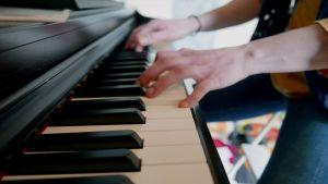 Pianoa soittavat kädet lähikuvassa