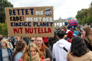 """En klimatdemonstrant i Tyskland bär ett plakat med texten: """"Rädda världen, det är den enda planeten med Nutella"""""""