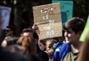 "En klimatdemonstrant med ett plakat med texten ""CO2 is in the air."""