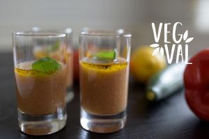 En vegetarisk gazpacho i glas. Bilden har kort skärpedjup men i bakgrunden kan man skönja en gurka och en citron. Högst uppe i höger hörn finns Vegval/Vegevalintas logotyp.