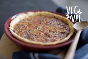 En vegetarisk lökpaj. Bilden har kortskärpedjup och högst uppe till höger finns Vegval/Vegevalintas logotyp.