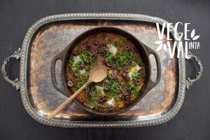 En vegetarisk Shaksuka i en gjutjärnsgryta på en silverbricka. Högs upp till höger finns Vegval/Vegevalintas logotyp.