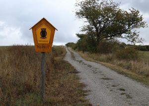 En skylt med texten hainich och en uggla på i förgrunden, och en ringlande sandväg ut i landskapet.