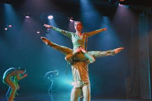 I förgrunden en man och kvinna som dansar. Kvinnan är lyft i mannens famn och har benen och armarna utsträckta åt sidan. I bakgrunden fler dansare nedböjda som på huk.