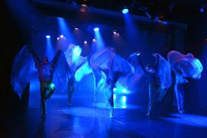 Flera dansare på scen med olika skynken som fladdrar.