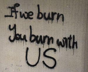 Betongvägg med graffititexten ''If we burn, you burn with us''.