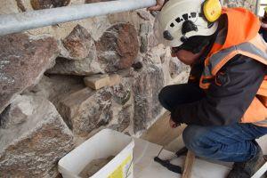 Arkeologi Kari Uotila katsoo muurissa oleva aaukkoa.